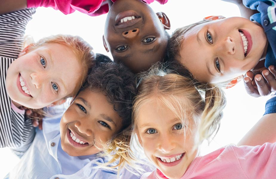 Looking up into huddle of multiracial kids smiling after seeing a pediatric dentist