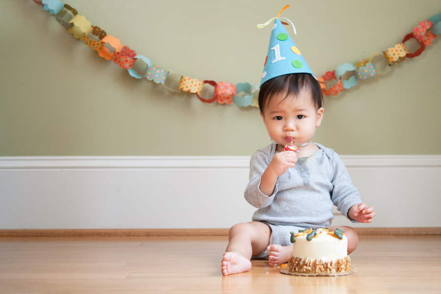 Dark-haired baby at their first birthday eats a cake before visiting the dentist for the first time